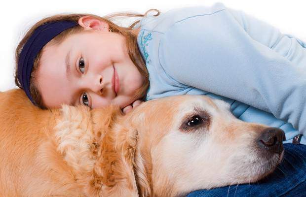 A young girl and golden retriever cuddle